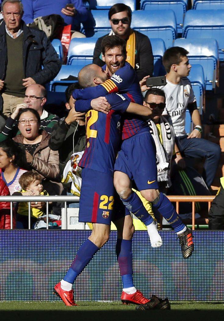 Barcelona's Aleix Vidal celebrates with Lionel Messi, right, after scoring his side's third goal during the Spanish La Liga soccer match between Real Madrid and Barcelona at the Santiago Bernabeu stadium in Madrid, Spain, Saturday, Dec. 23, 2017. (AP Photo/Francisco Seco)